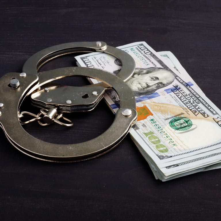 Ned L Polk Incorporated   handcuffs laying over money on a table
