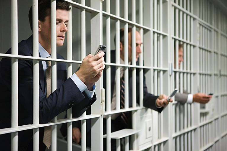 Ned L Polk Incorporated   Man in jail cell looking at a cell phone and dialing a number