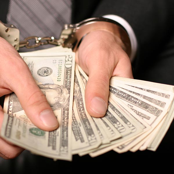 Ned L Polk Incorporated   handcuffed person's hands holding money and wearing a suit